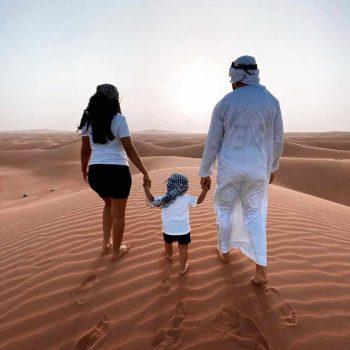family on sand dunes dubai